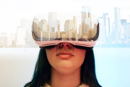 Photo for Double exposure of brunette girl wearing virtual reality headset and modern city with skyscrapers - Royalty Free Image
