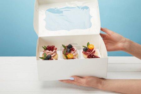 Photo pour Vue partielle de la boîte de fixation de femme avec des petits gâteaux isolés sur le bleu - image libre de droit
