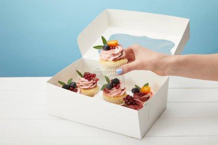 Photo pour Vue recadrée de femme retenant le gâteau doux d'isolement sur le bleu - image libre de droit