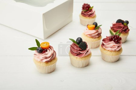 Photo for Cupcakes with berries and cream on white surface - Royalty Free Image