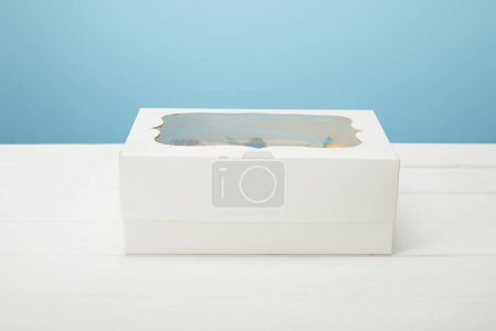 Photo for Box with cupcakes on white surface isolated on blue - Royalty Free Image