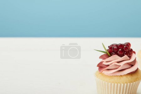 Photo for Tasty cupcake with garnet and cream on white surface isolated on blue - Royalty Free Image