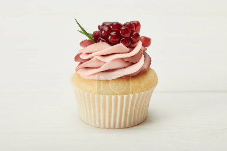 Photo for Tasty cupcake with cream and garnet on white surface - Royalty Free Image