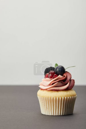 Photo for Cupcake with cream, garnet, grape and blackberry on dark surface isolated on grey - Royalty Free Image