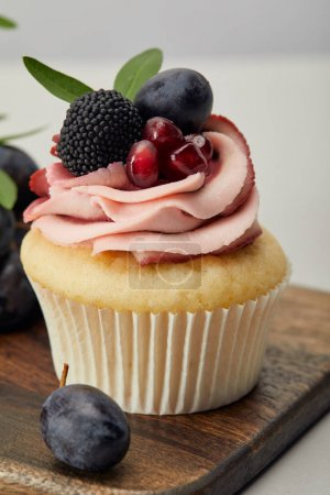 Photo for Tasty sweet cupcake with berries on wooden cutting board - Royalty Free Image