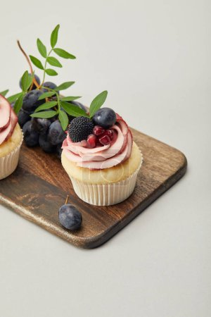 Photo for Cupcakes with grapes on cutting board isolated on grey - Royalty Free Image