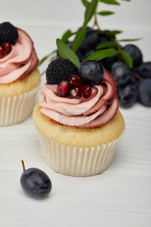 Photo for Selective focus of cupcakes with cream and grapes on white surface - Royalty Free Image