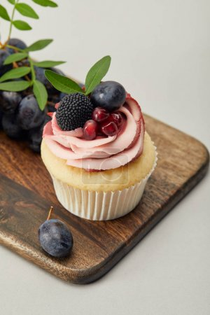 Photo for Cupcake with cream and grapes on cutting board isolated on grey - Royalty Free Image