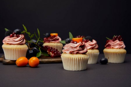Photo for Sweet cupcakes with berries and fruits on grey surface isolated on black - Royalty Free Image