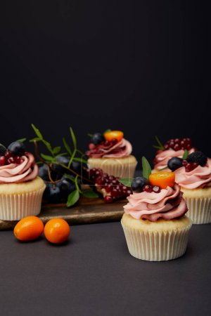 Photo for Cupcakes with cream, fruits and berries on grey surface isolated on black - Royalty Free Image