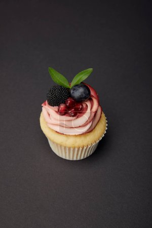 Photo for Cupcake with cream, garnet, grape and blackberry on black surface - Royalty Free Image