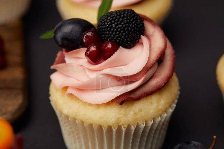 sweet cupcake with cream, garnet, blackberry and grape