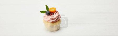 Foto de Foto panorámica de cupcake con kumquat, granate y uva en la superficie blanca - Imagen libre de derechos