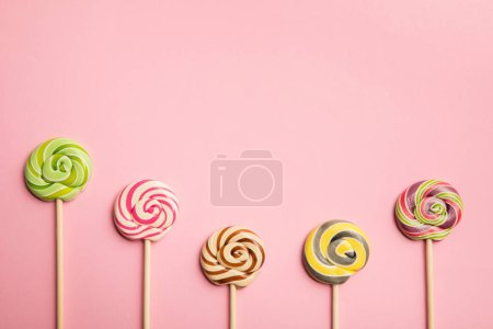 top view of delicious multicolored lollipops on wooden sticks on pink background