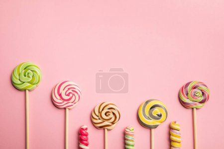 Photo for Top view of delicious swirl lollipops on wooden sticks on pink background with copy space - Royalty Free Image