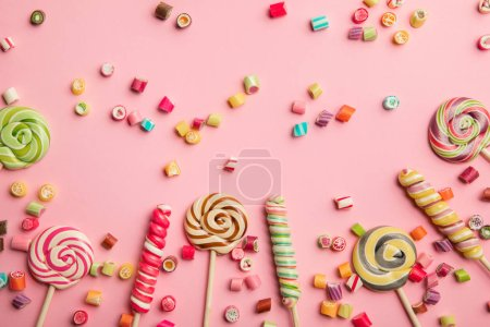 Photo for Top view of delicious multicolored candies and lollipops on pink background - Royalty Free Image