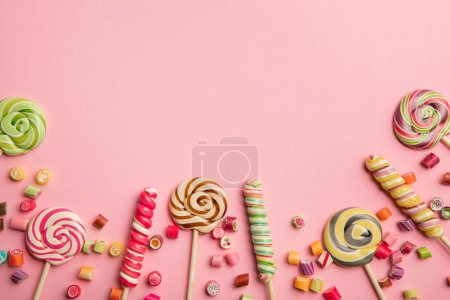 Photo for Top view of delicious multicolored swirl lollipops on wooden sticks and candies on pink background - Royalty Free Image