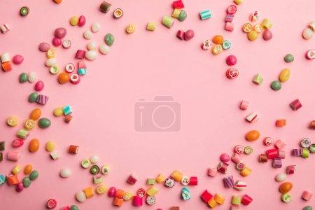 Photo pour Vue supérieure des bonbons multicolores dispersés sur le fond rose avec l'espace de copie - image libre de droit