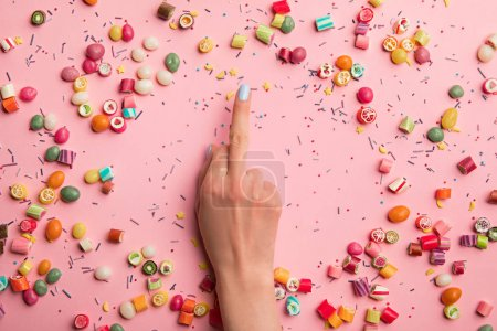 Photo for Cropped view of woman showing middle finger near multicolored candies and sprinkles scattered on pink background - Royalty Free Image