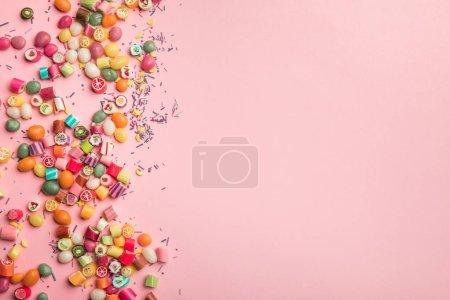 Photo pour Vue du haut des bonbons multicolores et saupoudre dispersés sur le fond rose avec l'espace de copie - image libre de droit