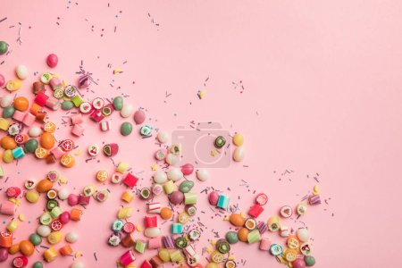 Photo for Top view of colorful candies and sprinkles scattered on pink background with copy space - Royalty Free Image