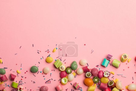 Photo for Top view of colorful sweet candies and sprinkles scattered on pink background with copy space - Royalty Free Image