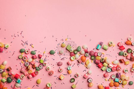 Photo for Top view of colorful tasty candies and sprinkles scattered on pink background with copy space - Royalty Free Image