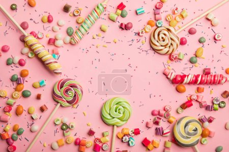 Photo for Top view of delicious multicolored lollipops, caramel candies and sprinkles on pink background - Royalty Free Image