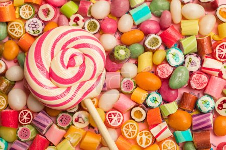 Photo for Top view of bright delicious multicolored caramel candies and lollipop - Royalty Free Image