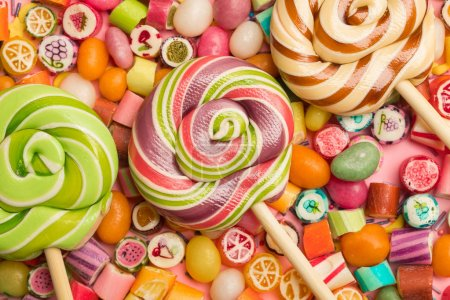 Photo for Top view of bright delicious multicolored caramel candies and lollipops on wooden sticks - Royalty Free Image