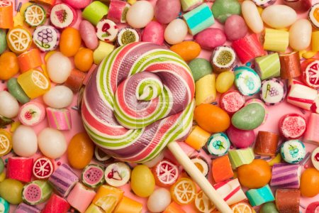 Photo for Top view of bright delicious multicolored caramel candies and swirl round lollipop on wooden stick - Royalty Free Image