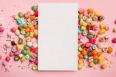 """Постер, картина, фотообои """"верхний вид вкусных разноцветных конфет и белой карты с копией пространства на розовом фоне"""""""
