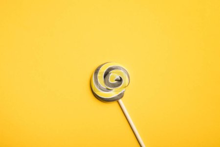 Photo for Top view of delicious multicolored swirl lollipop on wooden stick on yellow background - Royalty Free Image