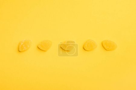 Photo for Top view of delicious sugary jellies in row on yellow background - Royalty Free Image