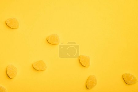 Photo for Top view of delicious sugary jellies scattered on yellow background - Royalty Free Image