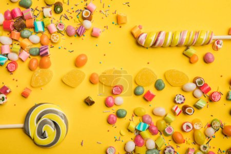 Photo for Top view of delicious multicolored candies, jellies, sprinkles and lollipops on yellow background - Royalty Free Image