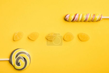 Photo for Top view of delicious  jellies and multicolored lollipops on yellow background - Royalty Free Image