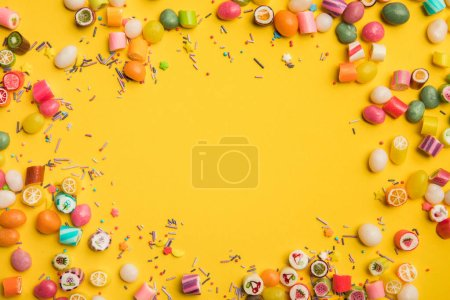 Photo for Frame of multicolored candies and sprinkles scattered on yellow background with copy space - Royalty Free Image