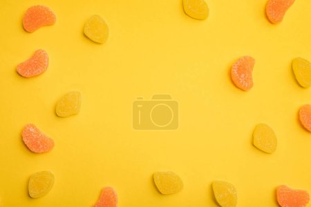 Photo for Top view of delicious orange and lemon jellies scattered on yellow background - Royalty Free Image