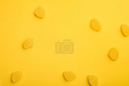 Photo for Top view of delicious lemon jellies scattered on yellow background - Royalty Free Image