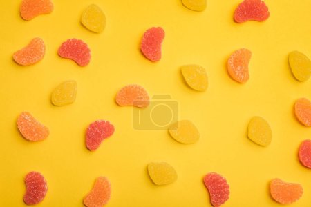 Photo for Top view of delicious lemon, grapefruit and orange jellies scattered on yellow background - Royalty Free Image