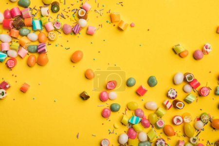 Photo for Top view of multicolored tasty sweets scattered on yellow background with copy space - Royalty Free Image