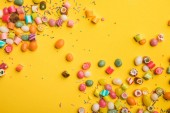 """Постер, картина, фотообои """"top view of multicolored tasty sweets scattered on yellow background with copy space"""""""