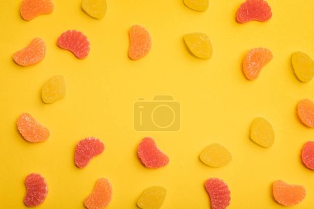 Photo for Top view of delicious lemon, grapefruit and orange jellies on yellow background with copy space - Royalty Free Image