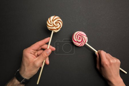 Photo for Cropped view of man and woman holding sweet lollipops on wooden sticks on black background - Royalty Free Image