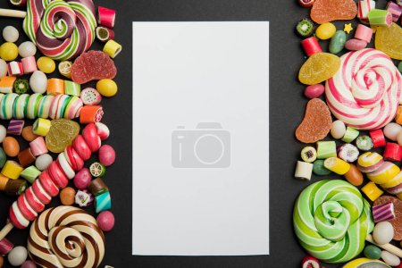 Photo for Top view of tasty multicolored caramel sweets and lollipops around white empty card on black background with copy space - Royalty Free Image