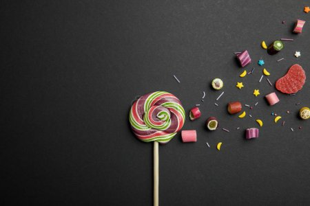 Photo for Top view of delicious multicolored round lollipop on wooden stick with candies and sprinkles on black background - Royalty Free Image