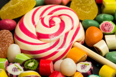Photo for Close up view of bright lollipop among fruit caramel multicolored candies - Royalty Free Image