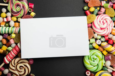 Photo for Top view of delicious multicolored sweets and blank white card on black background - Royalty Free Image