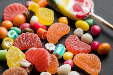 Photo for Selective focus of delicious caramel and jelly sweets on black background - Royalty Free Image
